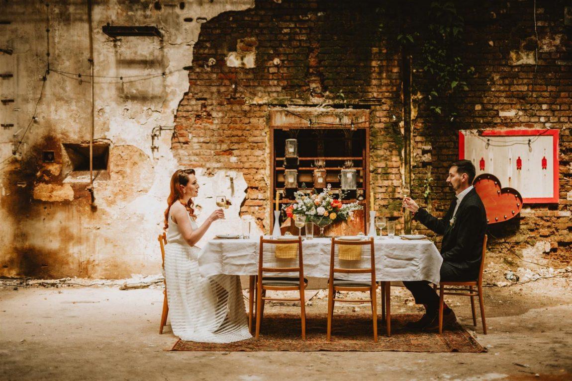 nevěsta a ženich sedí u stolu ve staré továrně, industriální udržitelná svatba