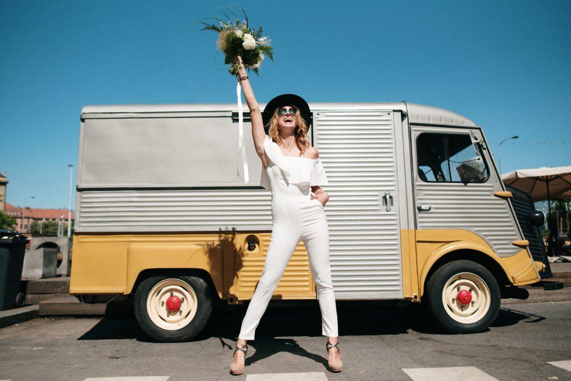 Nevěsta stojí před vanem v bílém svatebním overalu, v ruce kytici