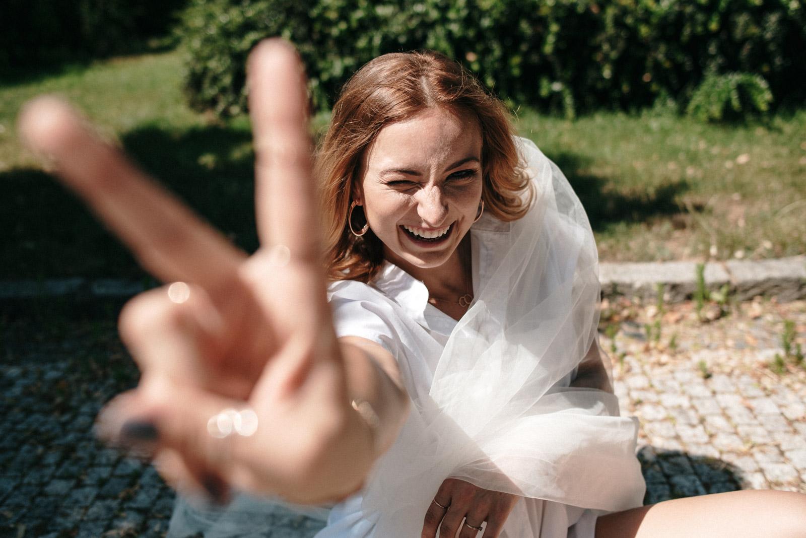 Nevěsta se směje a ukazuje rukou vé