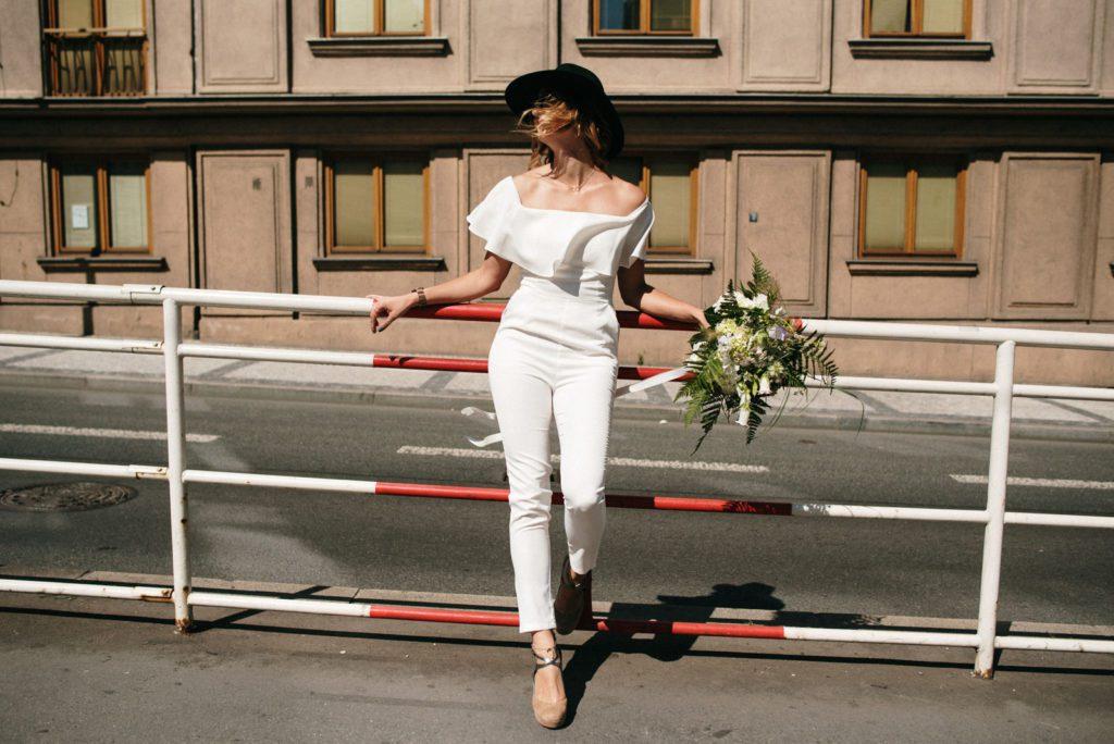 Nevěsta v klobouku a bílém overalu se opírá o zábradlí