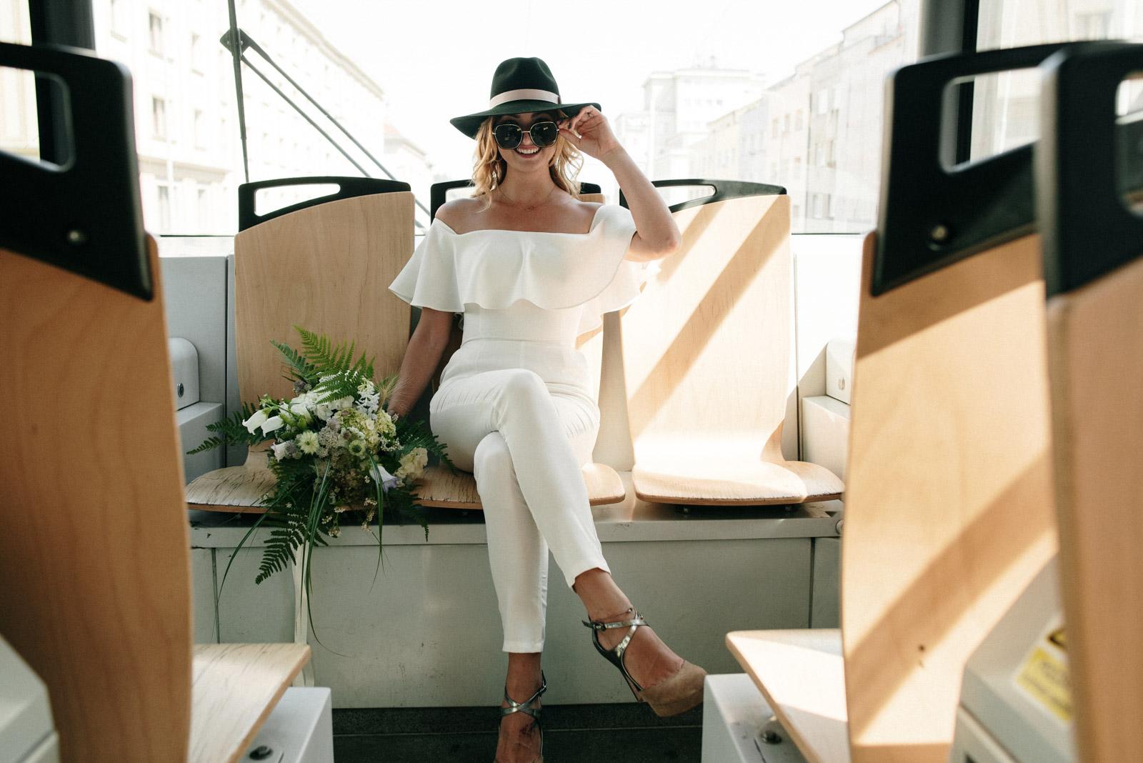 Nevěsta v bílém svatebním overalu sedí v tramvaji, v ruce kytici