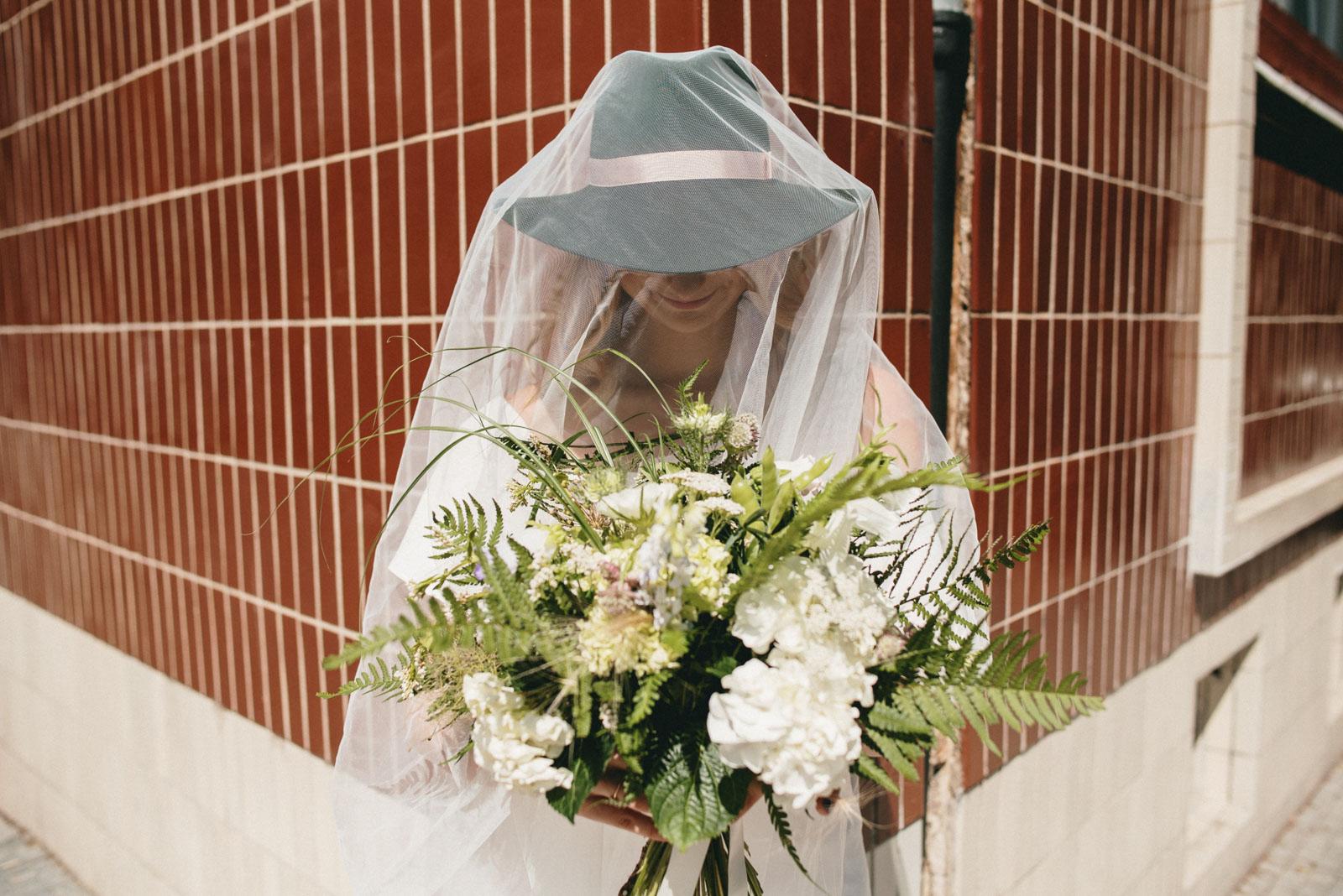 nevěsta zahalená do závoje drží svatební kytici z lučního kvítí a kapradin